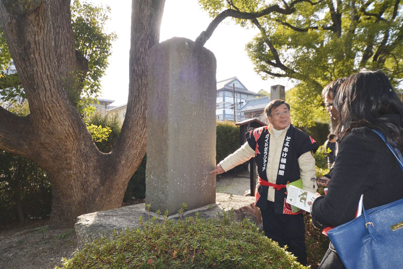 桶狭弔古碑に記されている文章を読みながら説明する桶狭間ガイドボランティアの堀田会長